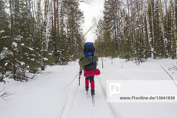 Rückansicht eines Mannes mit Rucksäcken beim Skifahren auf schneebedecktem Feld
