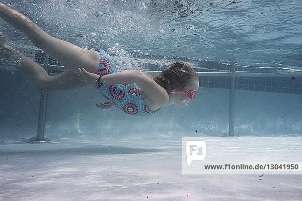 Mädchen schwimmt unter Wasser im Pool