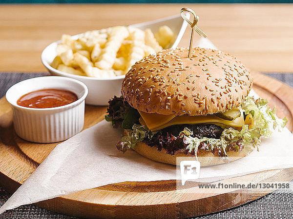 Nahaufnahme eines mit Soße servierten Burgers auf dem Tisch