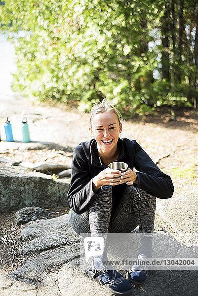 Schrägaufnahme einer fröhlichen Frau  die auf einem Campingplatz sitzt und Kaffee trinkt