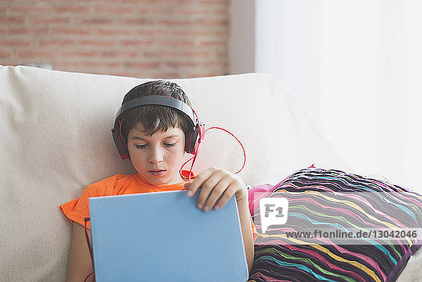 Boy using tablet computer while listening to music on sofa