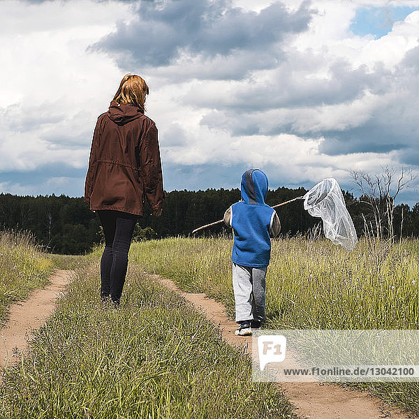 Rückansicht des Sohnes  der ein Schmetterlingsnetz hält  während die Mutter vor stürmischen Wolken auf dem Feld steht