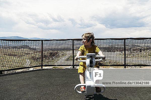 Carefree girl playing on rocking horse at playground
