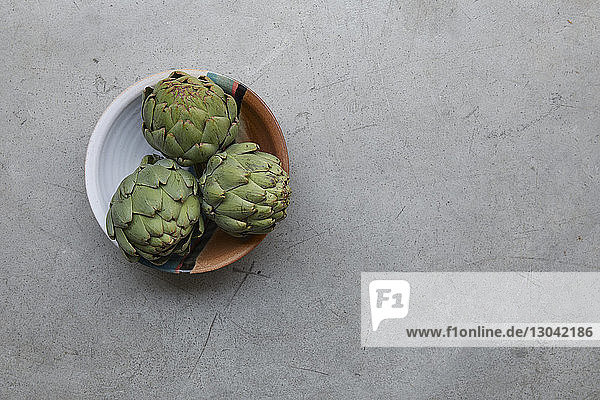 Close-up of healthy artichokes in bowl on table