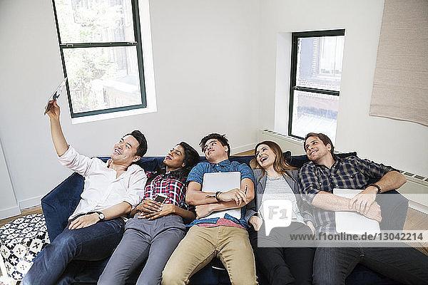 Fröhliche Geschäftsleute  die sich im kreativen Büro auf dem Sofa zurücklehnen