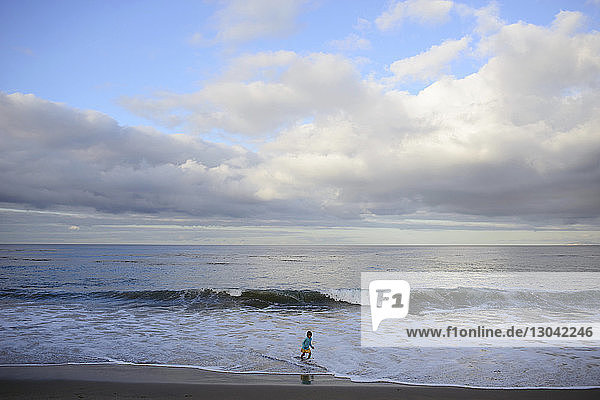 Mädchen spielt im Meer am Laguna Beach gegen bewölkten Himmel
