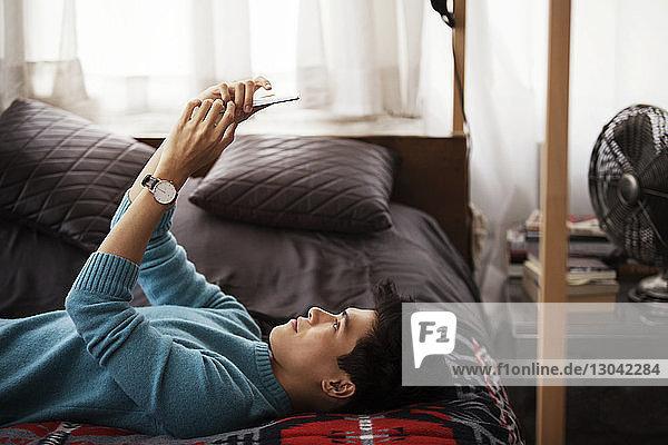 Seitenansicht eines Mannes  der ein Smartphone benutzt  während er zu Hause im Bett liegt