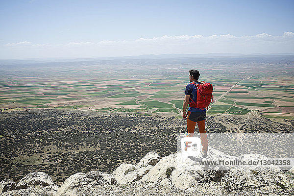 Rear view of man with backpack looking at view while standing on mountain against sky during sunny day