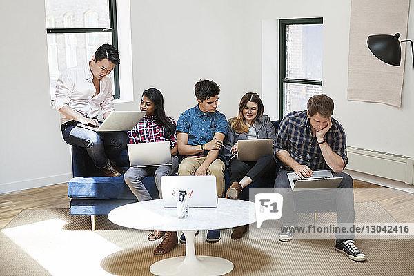 Kollegen  die im Kreativbüro an Laptops arbeiten