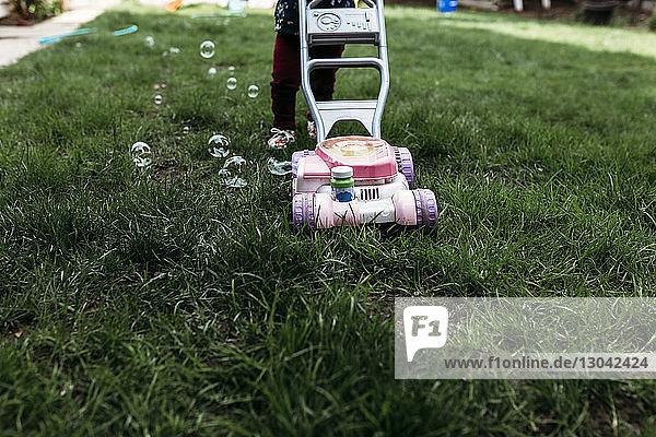 Niedriger Abschnitt eines Mädchens  das neben einem Blasenmäher im Rasen steht