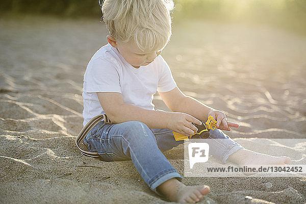 Kleiner Junge spielt mit Spielzeug  während er am Strand im Sand sitzt