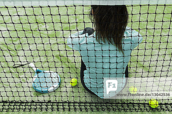 Rear view of woman sitting on tennis court by net