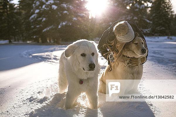 Woman kissing dog on snowy field
