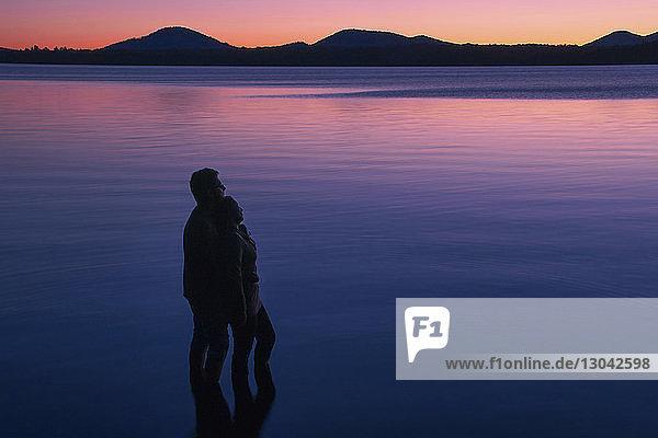 Hochwinkelansicht eines Paares  das im See vor Bergen und dramatischem Himmel steht