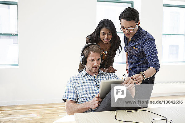 Multi-ethnic business people using tablet computer in creative office