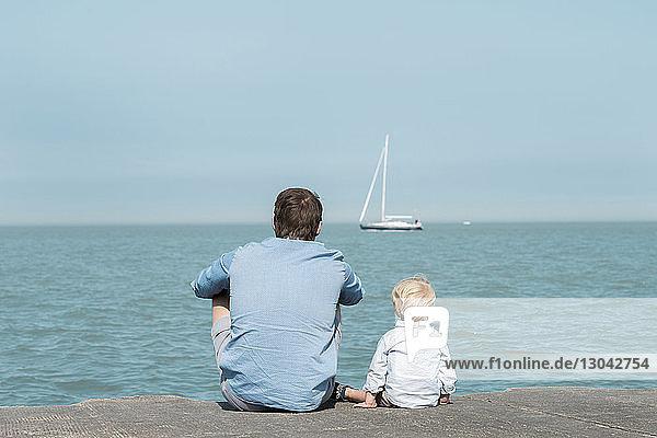 Rückansicht eines Vaters mit Sohn am Strand sitzend vor blauem Himmel am sonnigen Tag