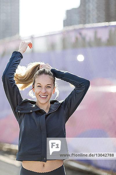 Porträt eines selbstbewussten Athleten  der bei sonnigem Wetter am Zaun steht und sich die Haare bindet