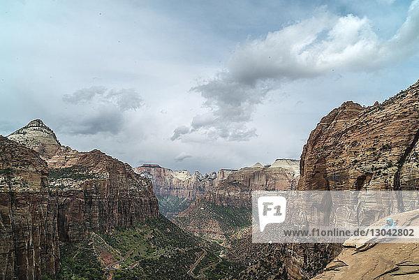 Wanderin sitzt auf felsigen Bergen vor bewölktem Himmel im Zion-Nationalpark