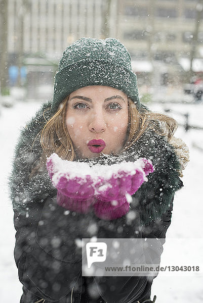 Portrait of woman blowing snow