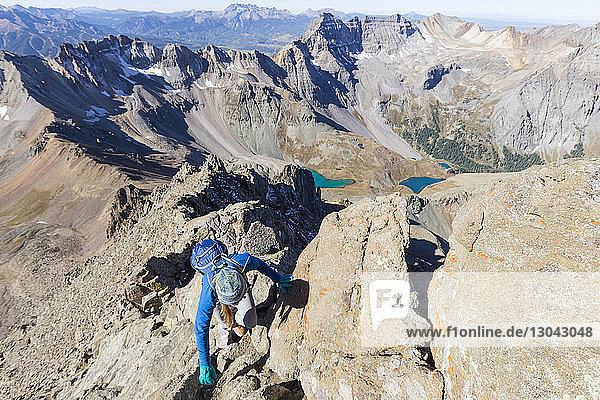 Hochwinkelaufnahme einer Wanderin  die an einem sonnigen Tag den Berg besteigt