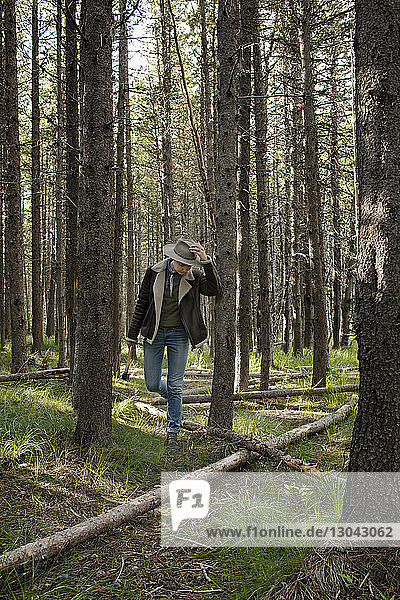 Female hiker walking amidst forest while holding axe