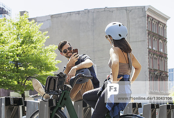 Glücklicher Mann fotografiert Frau  die in der Stadt auf dem Fahrrad sitzt