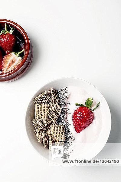 Draufsicht auf das Frühstück mit Erdbeeren auf weißem Hintergrund