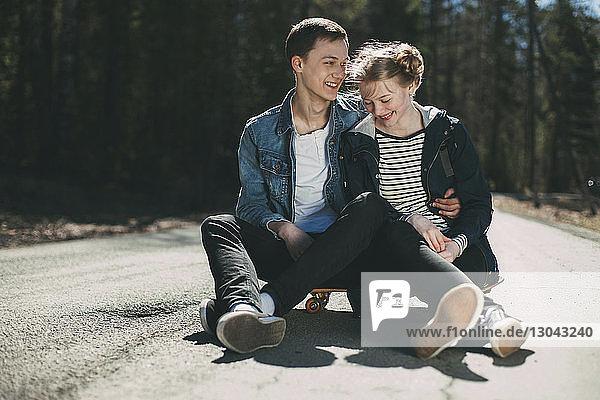 Glückliches junges Paar sitzt bei Sonnenschein auf einem Skateboard auf der Straße
