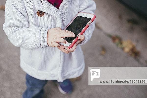 Niedriger Teil eines Mädchens  das ein Smartphone hält  während es auf einem Fußweg steht