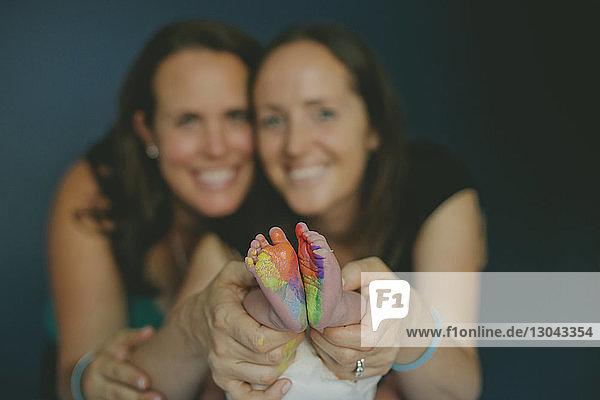 Porträt eines homosexuellen Paares  das die Füße eines kleinen Jungen mit buntem Stempel zeigt