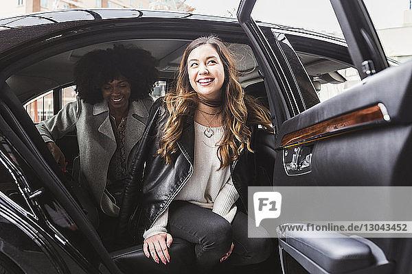 Fröhliche Geschäftsfrauen beim Aussteigen aus dem Auto