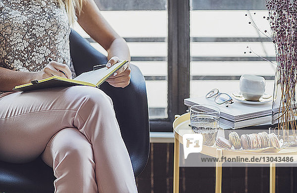 Close-up of businesswoman writing in diary while sitting on chair by table