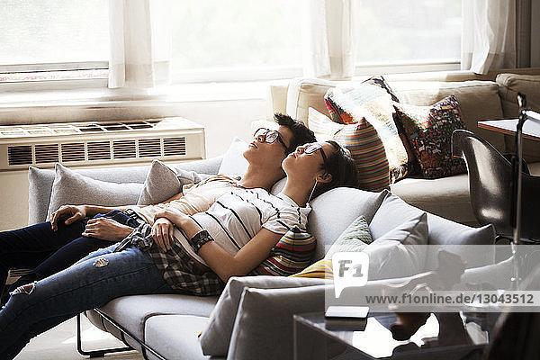 Entspanntes multi-ethnisches junges Paar  das zu Hause auf dem Sofa liegt