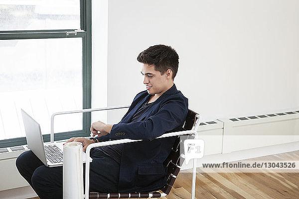 Seitenansicht eines glücklichen Geschäftsmannes mit Laptop im Kreativbüro Seitenansicht eines glücklichen Geschäftsmannes mit Laptop im Kreativbüro