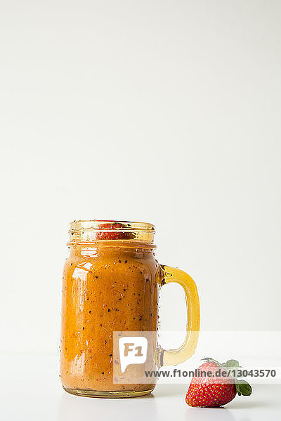 Close-up of smoothie in mason jar against white background