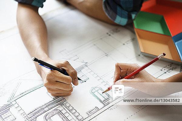 Beschnittenes Bild eines Paares  das zu Hause den Bauplan untersucht