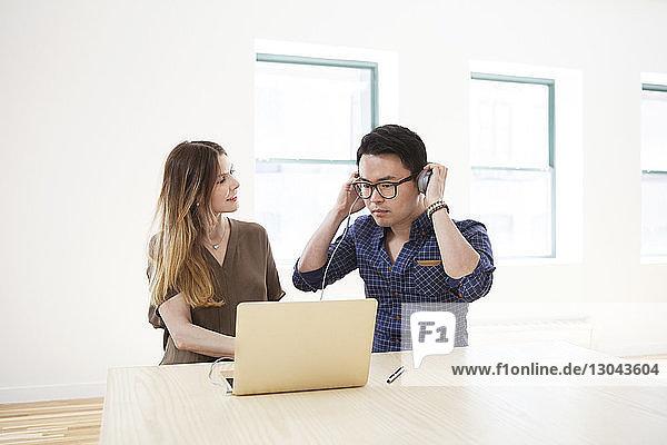 Geschäftsfrau betrachtet einen männlichen Kollegen  der Kopfhörer trägt  während er im Büro einen Laptop benutzt Geschäftsfrau betrachtet einen männlichen Kollegen, der Kopfhörer trägt, während er im Büro einen Laptop benutzt