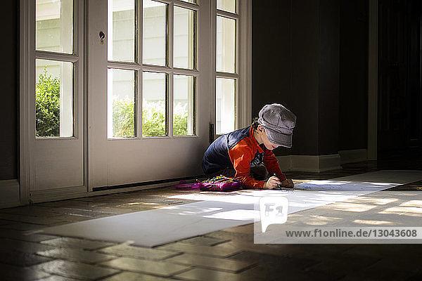 Junge zeichnet auf Papier  während er auf dem Boden an der Tür sitzt