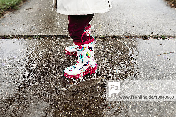Low section of girl wearing rubber boots while standing in puddle