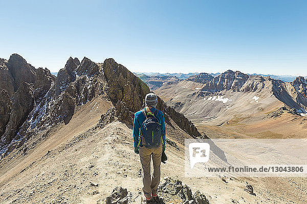 Rückansicht einer Frau  die auf dem Gipfel eines Berges vor klarem  blauem Himmel steht