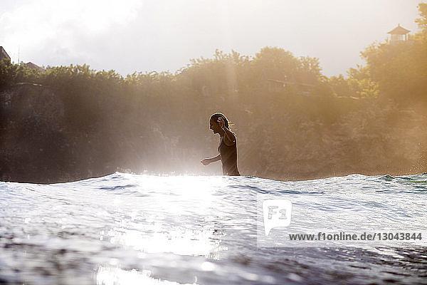 Seitenansicht einer glücklichen Frau  die im Meer geht