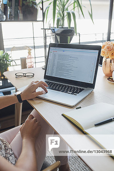 Cropped image of businesswoman using laptop computer at table in home office