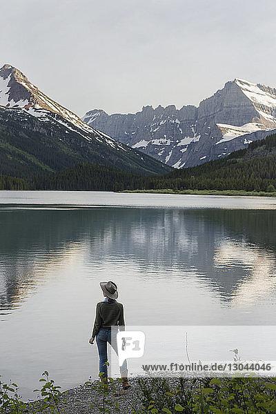 Rückansicht einer Wanderin  die am Ufer des Swiftcurrent Lake steht