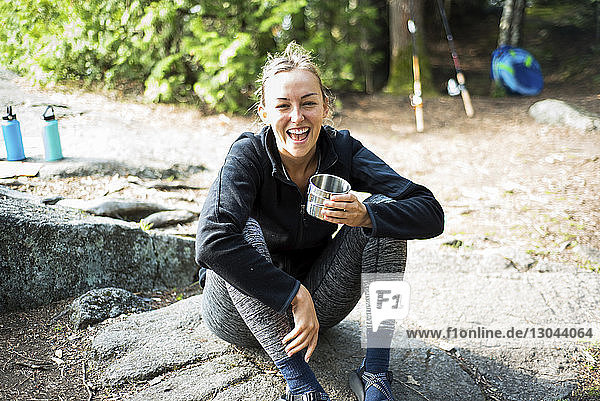 Cheerful woman having coffee while sitting at campsite