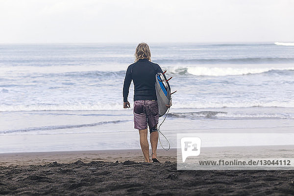 Rear view of man carrying surfboard while walking at beach towards sea