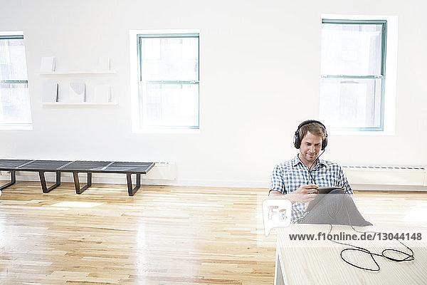 Geschäftsmann hört Musik über Tablet-Computer im Kreativbüro Geschäftsmann hört Musik über Tablet-Computer im Kreativbüro