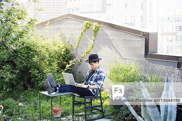 Man using laptop while sitting with feet up on table at terrace