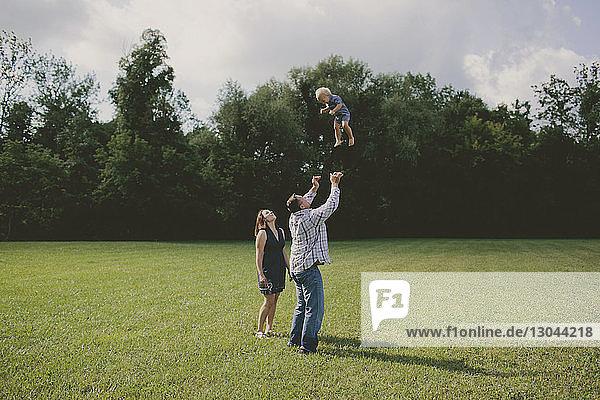 Frau sieht Mann an  der seinen Sohn in die Luft wirft
