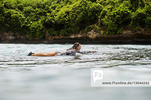 Side view of woman surfboarding on wave in sea