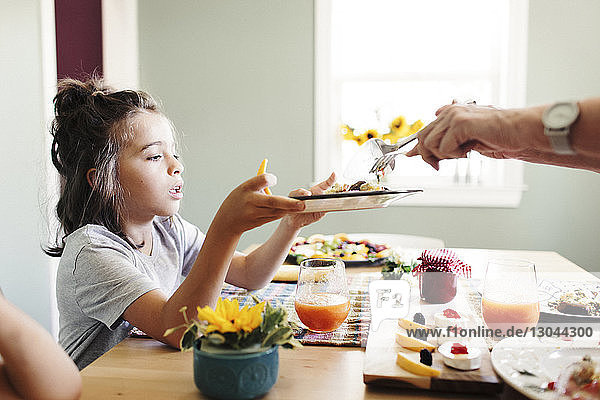Cropped hands of grandmother serving food to grandson